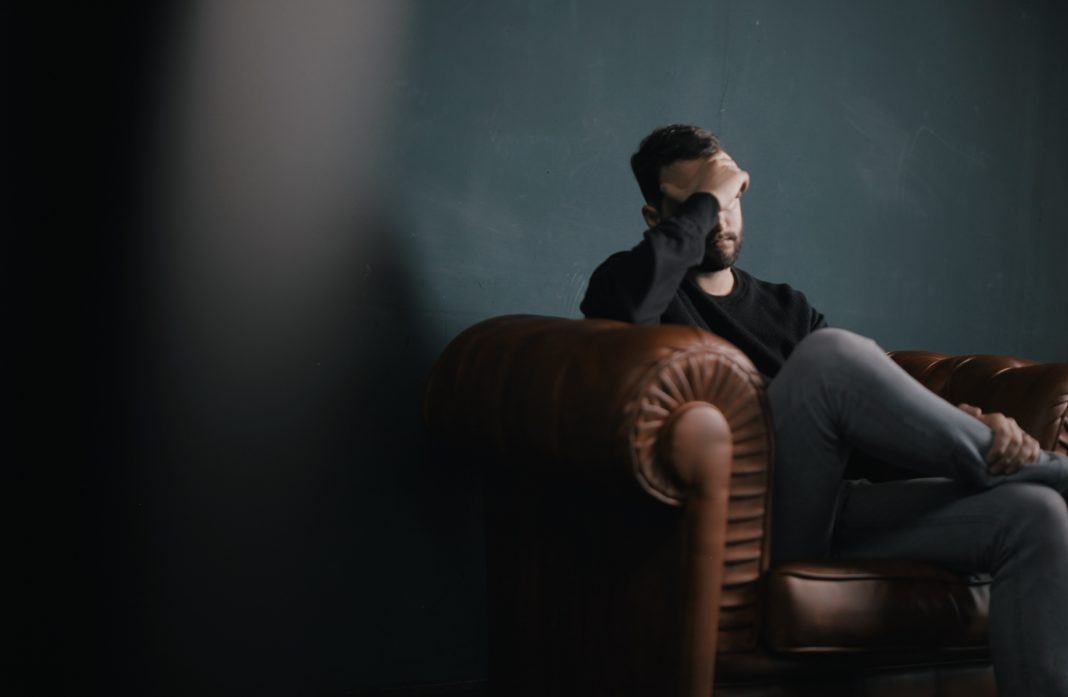 Stress In The Workplace With A Man With Head In Hands